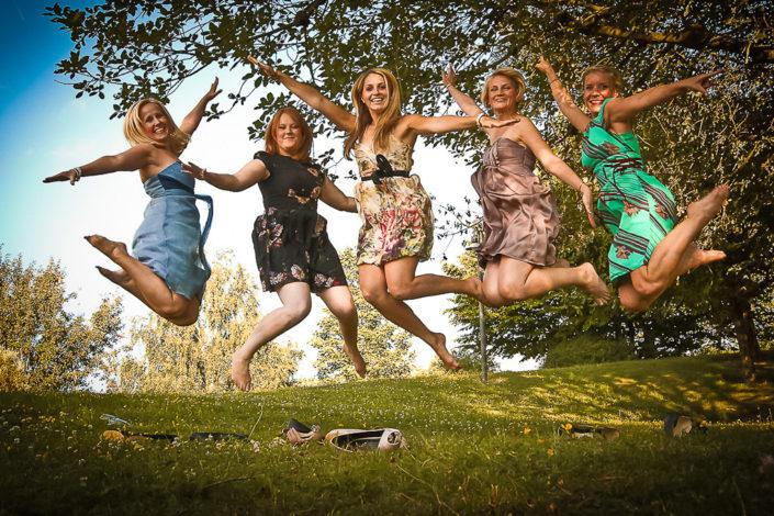 Hochzeitsgäste machen Luftsprünge auf einer grünen Wiese