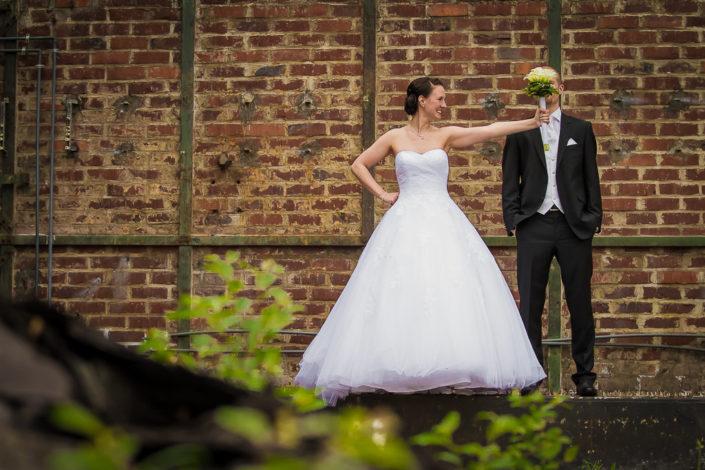 Bräutigam mit Brautstrauß vor dem Gesicht