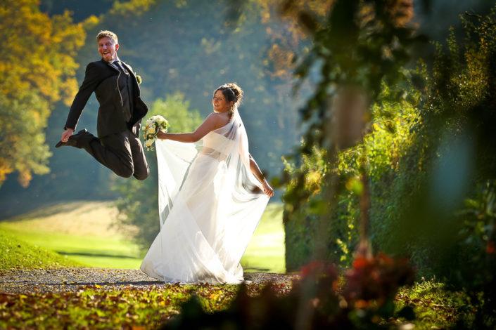 Foto vom Bräutigam der neben der Braut in die Luft springt