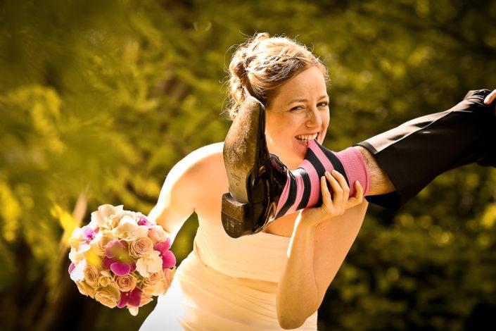 Braut beißt in die Socken des Bräutigams
